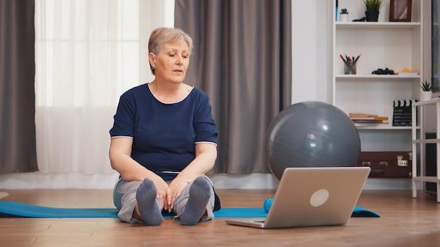 ノートパソコンでエクササイズレッスンを見ながら体を伸ばしてヨガマットに座っている老婆。ラップトップを使用してオンラインで新しい技術のレッスンを学ぶ引退した老人、スポーツと組み合わせた健康的なライフスタイル