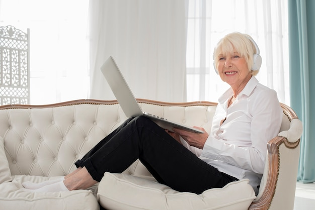 Old woman sitting on sofa with headphones and laptop