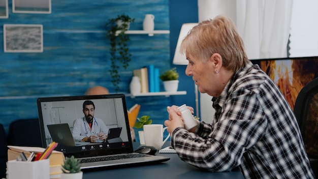Old woman sitting at table at home looking at laptop answering question about health talks with therapist by videoconference call application, holding pills flask remote medical consultation concept