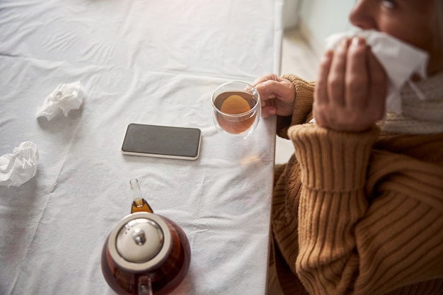 Old woman sitting at the table with cup of tea