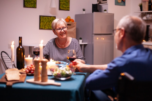 Old woman smiling at disabled husband in wheelchair during dinner.