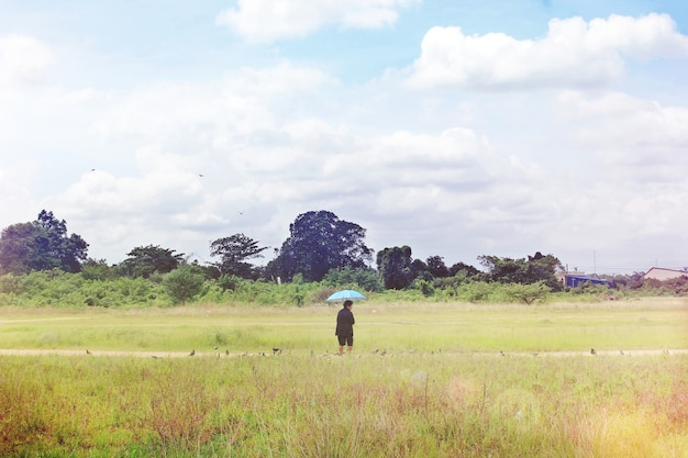 Old woman spread umbrella standing in the meadow.