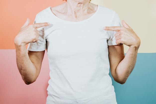 Старая женщина, стоящая над изолированным и улыбающимся красочным фоном. молодая женщина, одетая в белую футболку, пустое пространство футболки, копирование пространства, дизайн, торговый коммерческий снимок