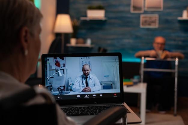 Старая женщина разговаривает с врачом на видеоконференции