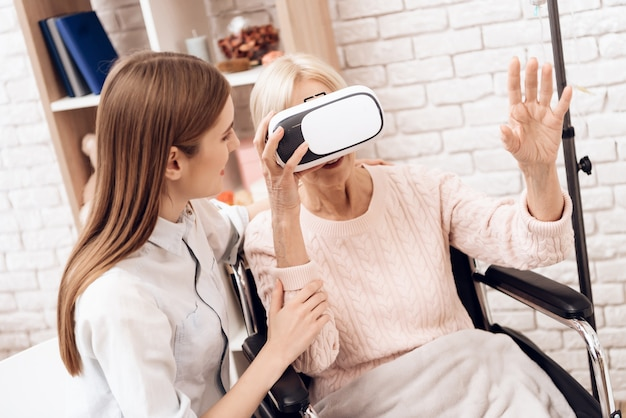 Old woman in virtual reality glasses at home.