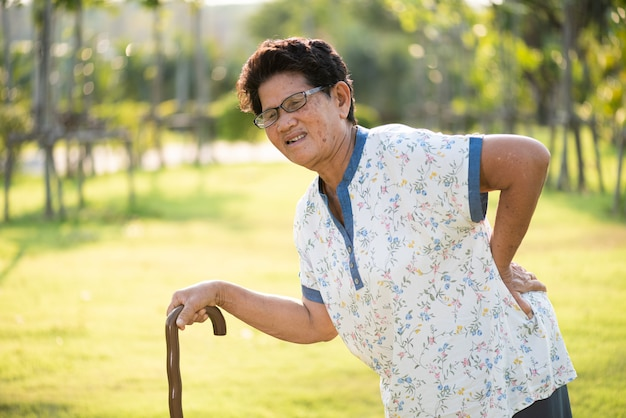 Old woman walking in park and having a back pain, backache.