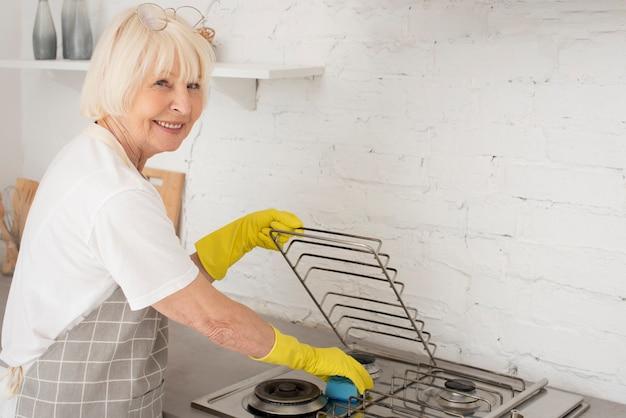 Пожилая женщина моет печь в перчатках