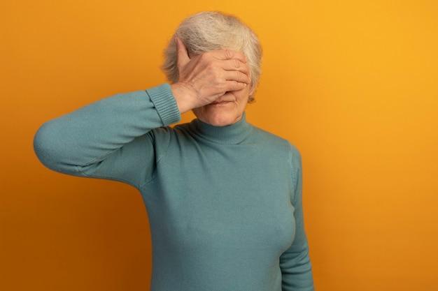 Vecchia donna che indossa un maglione blu a collo alto che copre gli occhi con la mano