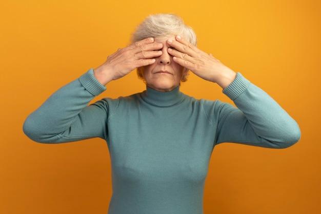 손으로 눈을 가린 파란색 터틀넥 스웨터를 입은 할머니