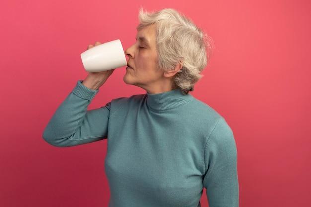 Vecchia donna che indossa un maglione a collo alto blu che beve una tazza di tè con gli occhi chiusi