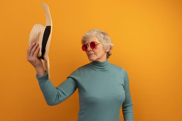Old woman wearing blue turtleneck sweater and sunglasses holding and looking at hat