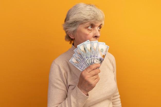 프로필 보기에 서 있는 크림색 터틀넥 스웨터를 입은 노부인은 복사 공간이 있는 주황색 벽에 격리된 뒤에서 올려다보는 돈을 들고 있습니다.