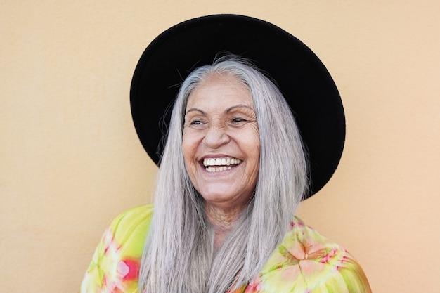 Old woman wearing hipster hat and smiling - joyful elderly person - concept of happiness