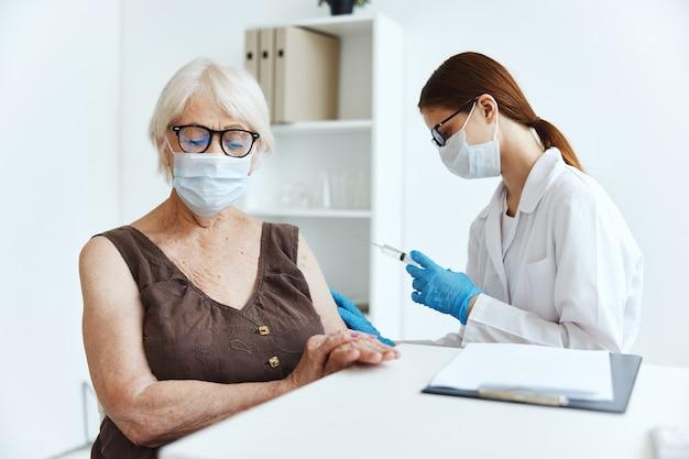 Старушка в медицинской маске в больнице для прививок covid паспорт