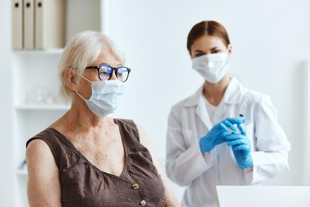 Старая женщина в медицинской маске в больнице для защиты иммунитета от прививок