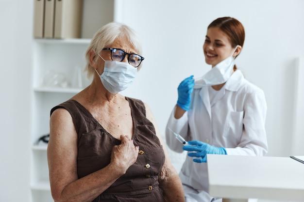 Пожилая женщина в медицинской маске в больнице для вакцинации паспорт вакцины