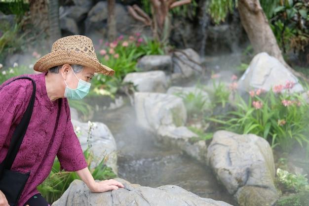 Старая женщина в медицинской маске отдыхает в саду