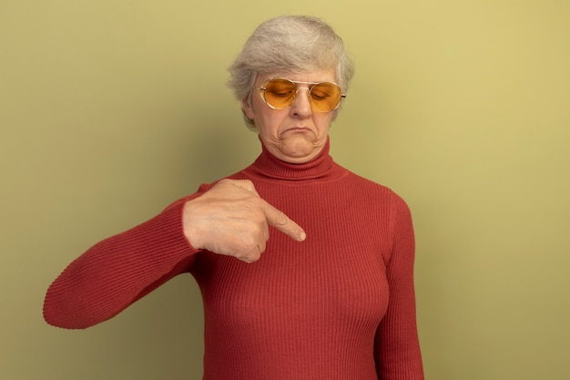 Old woman wearing red turtleneck sweater and sunglasses looking and pointing at her chest