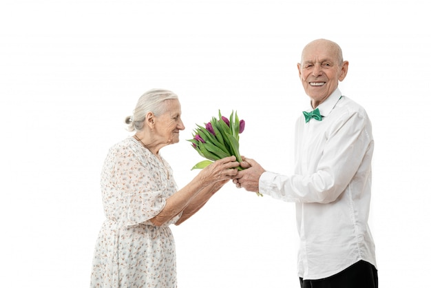Old woman in white dress smeling flowers that her senior husband gave her