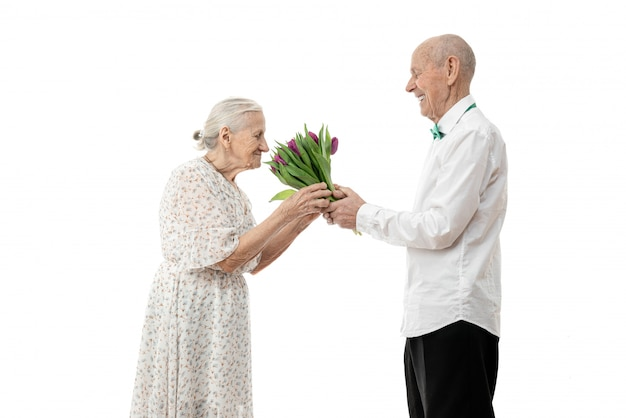 Old woman in white dress smelling flowers that her senior husband gave her