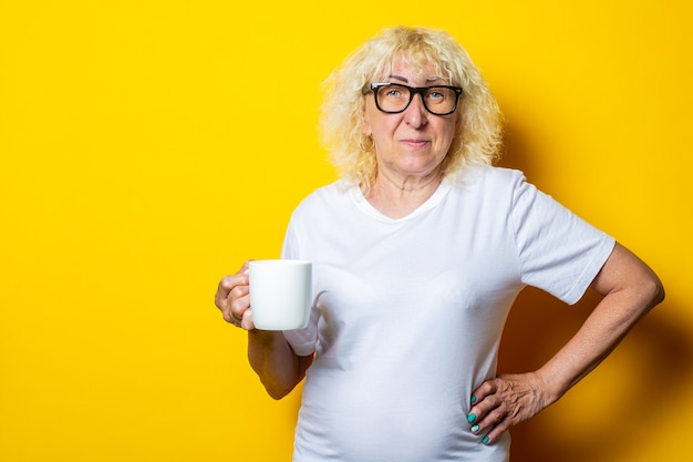 Old woman in white t-shirt and glasses holds a cup of tea on a yellow wall.