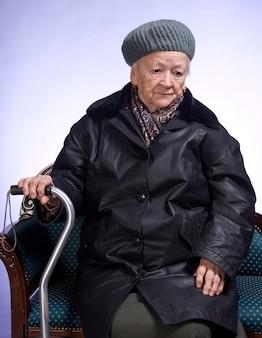 椅子に座っている冬のアウターウェアの杖を持つ老婆