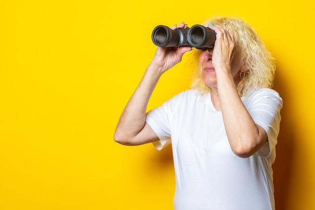 白いtシャツを着た笑顔の老婆が黄色い壁の双眼鏡で見ています。
