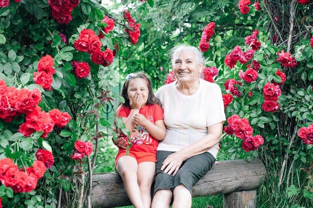 Snowwhite 미소와 소녀와 늙은 여자는 안뜰에서 벤치에 앉아 재미를 보내고있다