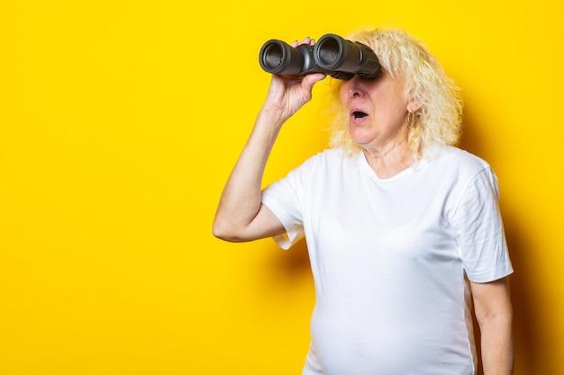 白いtシャツに驚いた顔をした老婆が黄色い壁の双眼鏡で見ています。