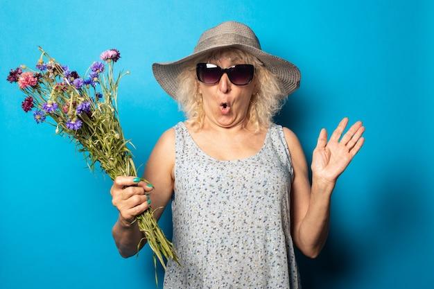 青い壁に花束を持ったつばの広い帽子とドレスに驚いた顔をした老婆。
