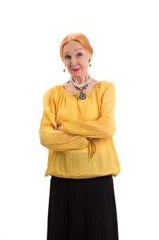 Старая женщина со скрещенными руками, уверенная в себе леди на белом фоне, остается верной своим принципам