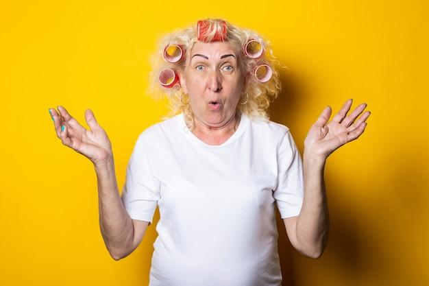 彼女の髪にカーラーを持つ老婆