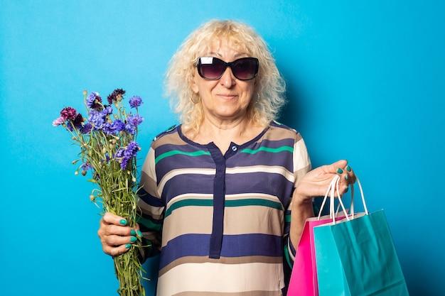 Старуха в очках держит хозяйственные сумки и букет цветов на синей стене.