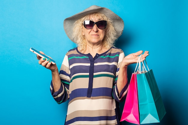 Old woman with glasses holds shopping bags and phone on blue wall.