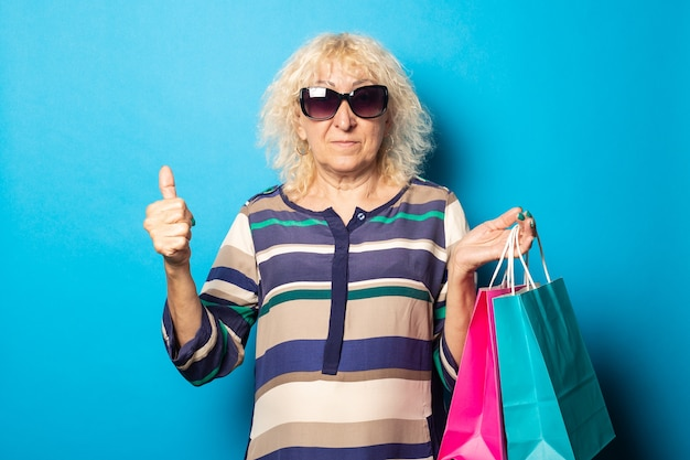 Old woman with glasses holds shopping bags and shows friendly, welcome gesture on blue wall.