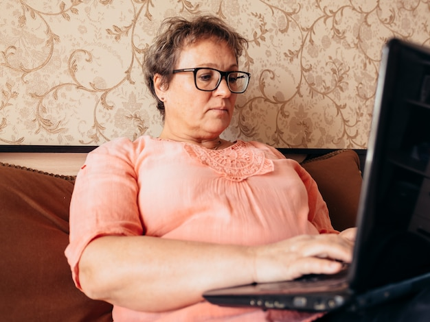 Old woman with glasses sitting at home working on a laptop, reading the news.