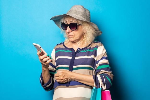 Старуха в шляпе и очках держит сумки для покупок и смотрит в свой телефон на синей стене.