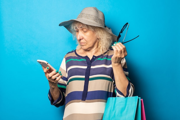Old woman with hat and glasses holds shopping bags and looks into her phone on a blue wall.