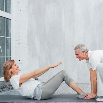 Old woman with her husband doing sit ups in living room