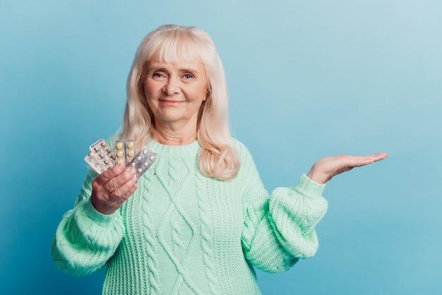 의료 제품을 들고 있는 노부인은 파란색 배경 위에 손 광고에 정제를 들고 있다