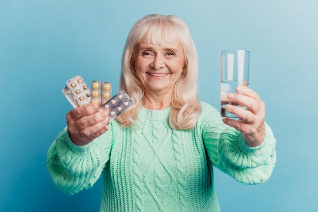 의료 제품 물을 가진 노부인은 파란색 배경 위에 정제를 손에 들고 있다