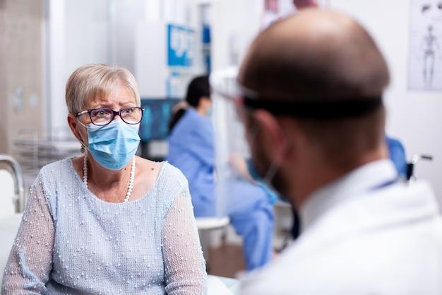 病室での診察中に医師を心配しているコロナウイルスの発生に対する保護フェイスマスクを持つ老婆