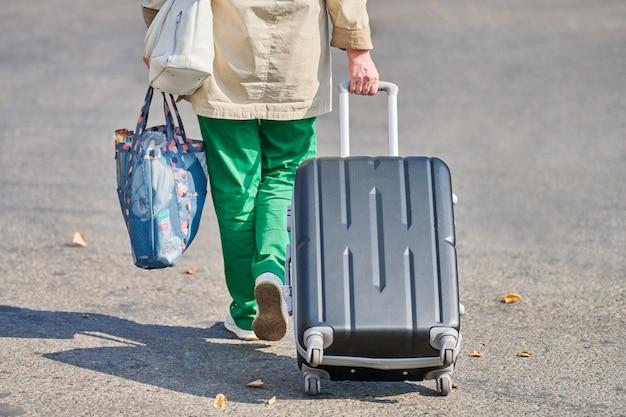 Старуха с чемоданом на колесах