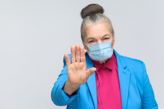 Old woman with surgical medical mask showing stop sign at camera