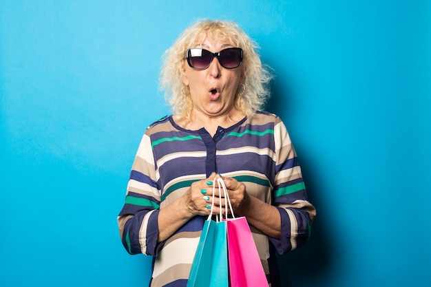 Old woman with surprised face holding shopping bags on blue wall.