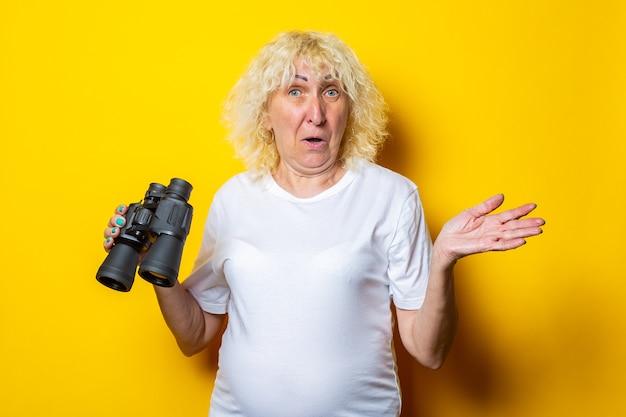 黄色の壁に双眼鏡を保持している白いtシャツで驚いた顔を持つ老婆。