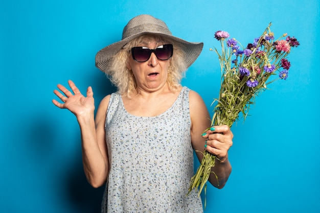 Old woman with a surprised face in a wide-brimmed hat and dress holding a bouquet of flowers on a blue surface