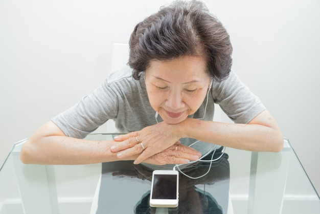 Old women  listening to music from mobile