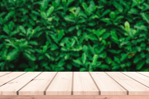 Старая деревянная доска с абстрактным фоном натуральных зеленых листьев для демонстрации продукта