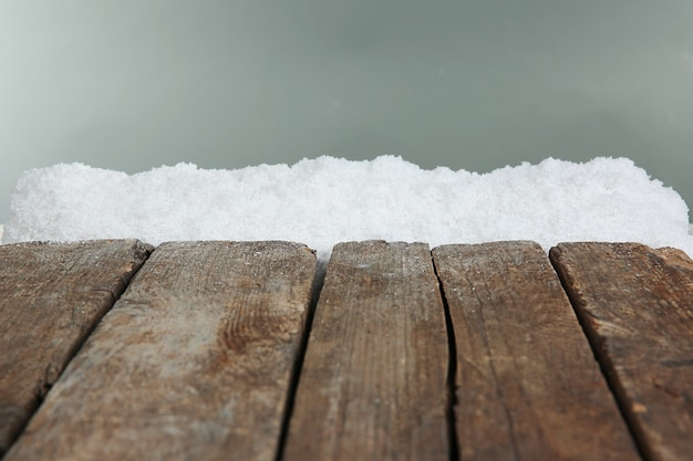 灰色の背景に雪の古い木の板